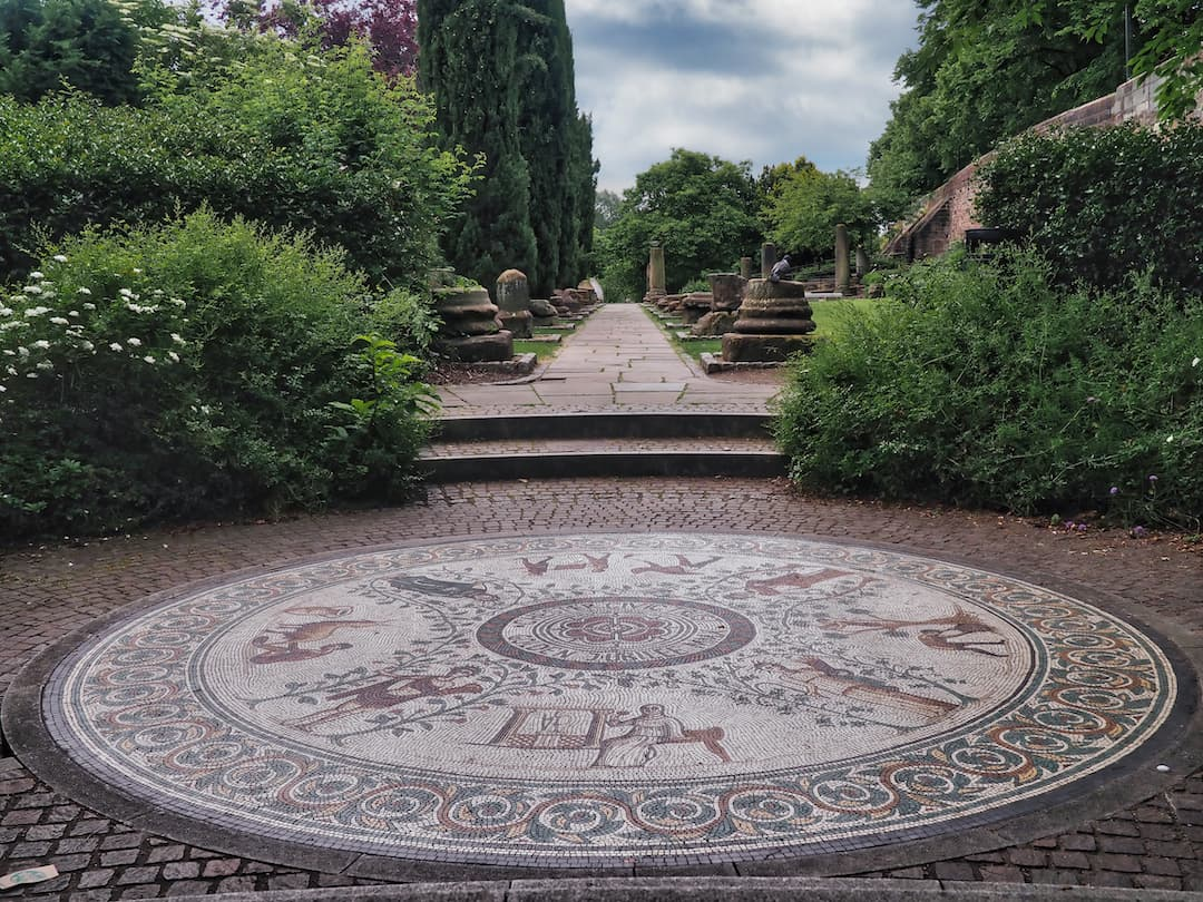 A circular mosaic in the foreground and a park with ancient stones in the background
