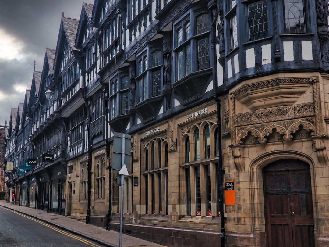 A row of sandstone buildings with black and white half-timbered facades