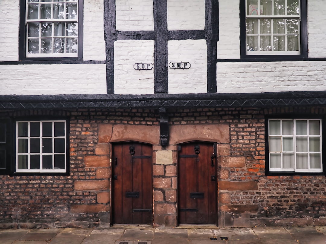A brick building with black and white half-timbered facade on the first floor