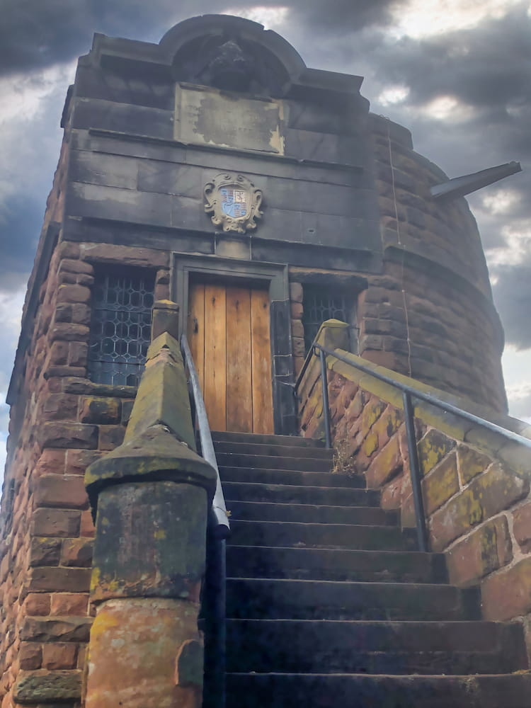Stone steps lead up to a wooden door on a tower