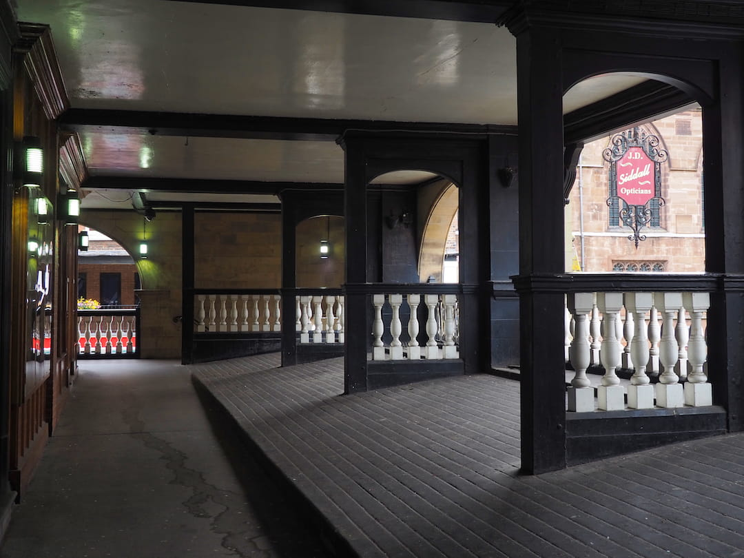 Am enclosed passageway with railings above the street to the right