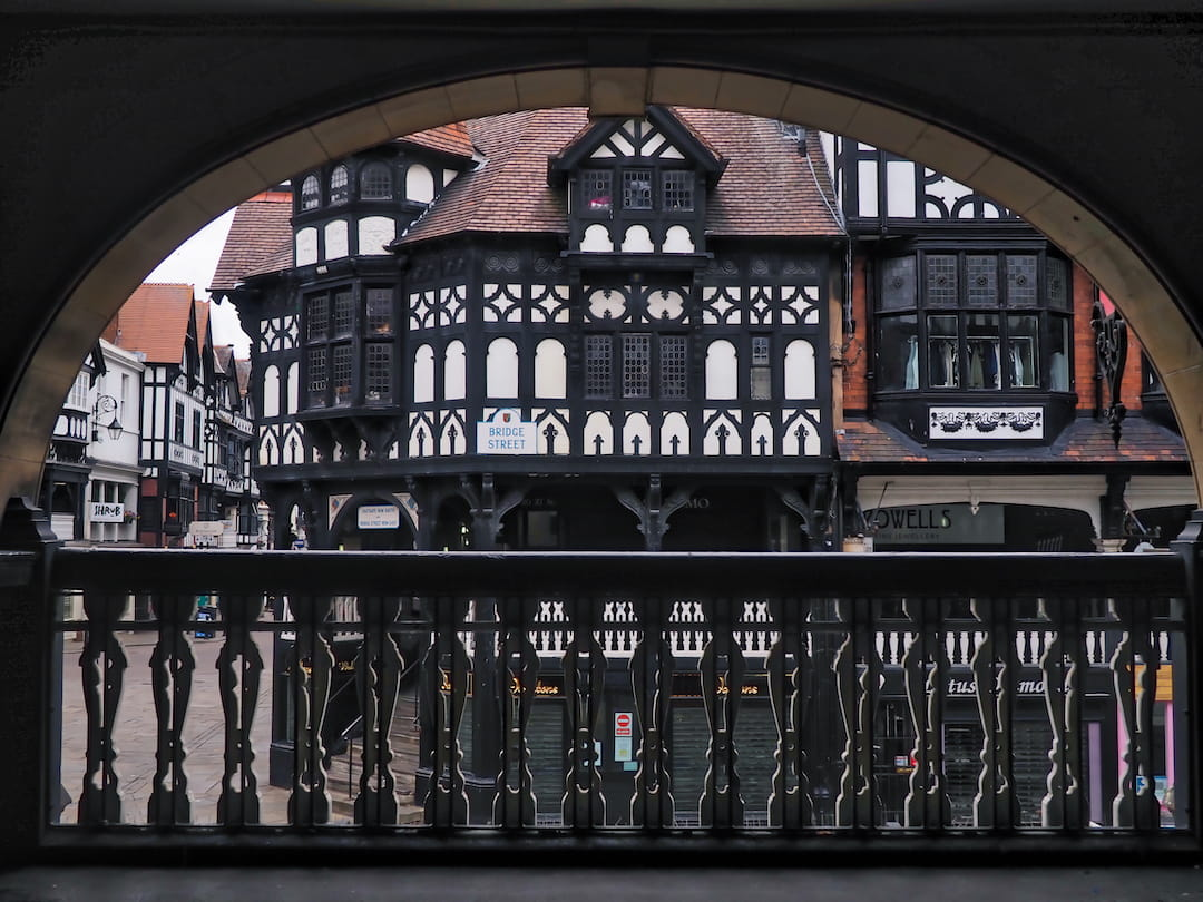 View of a black and white half-timbered building through an arch