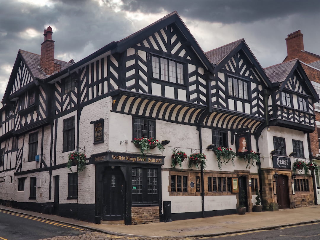 A whitewashed building with a black and white half-timbered facade on the first floor