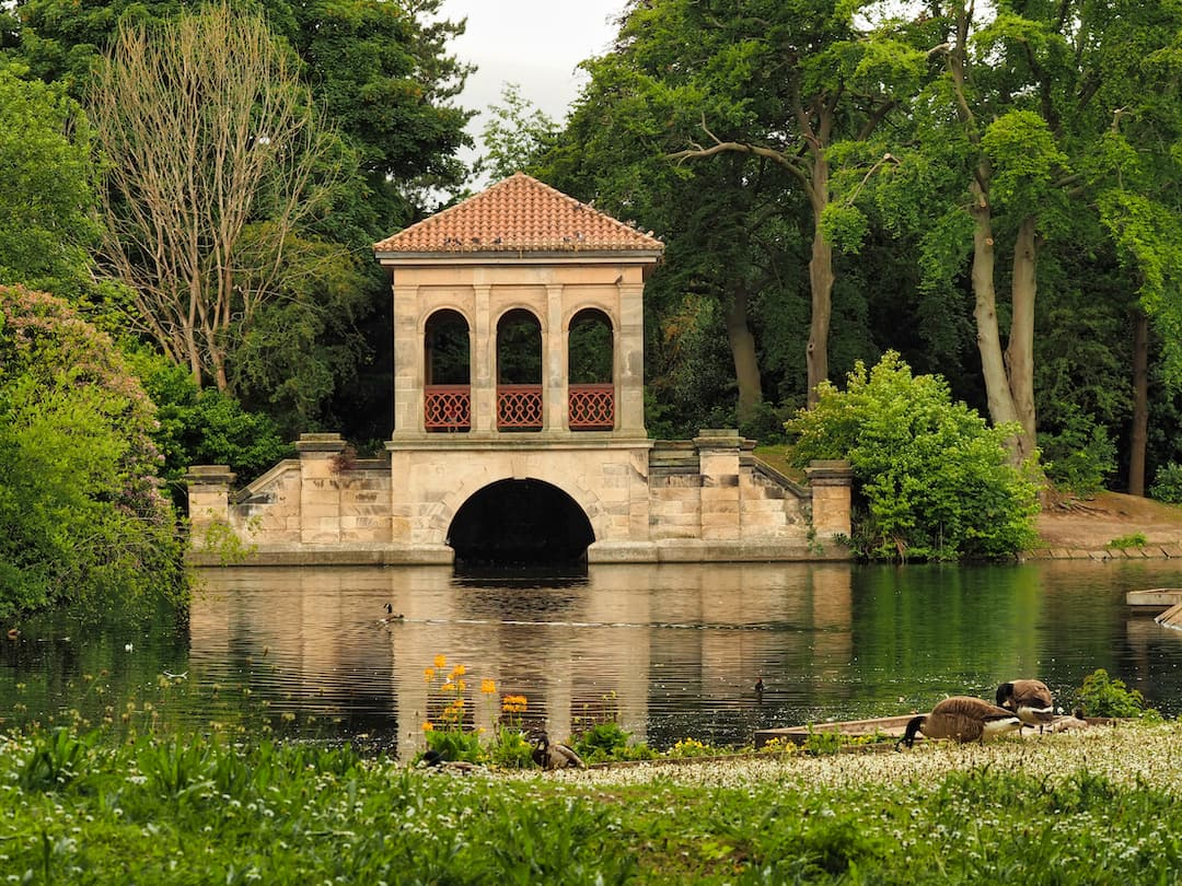 A bridge with a tower and three arches straddles a lake