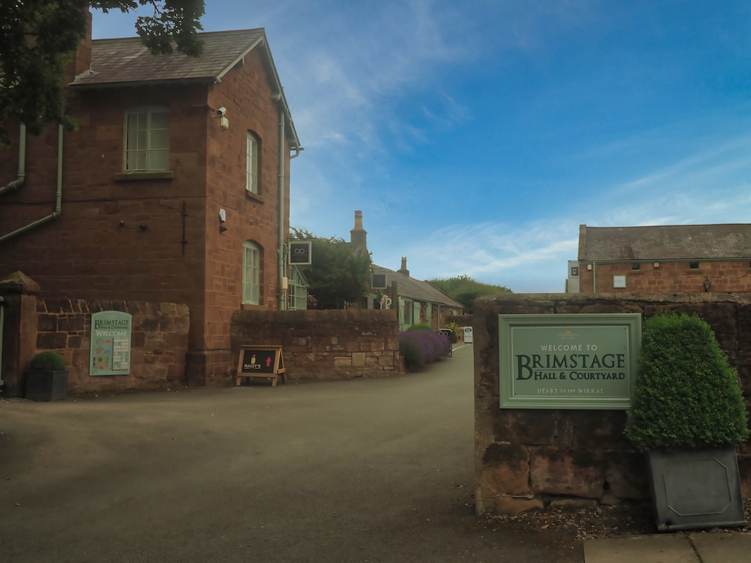 A sign for Brimstage Hall with sandstone buildings behind