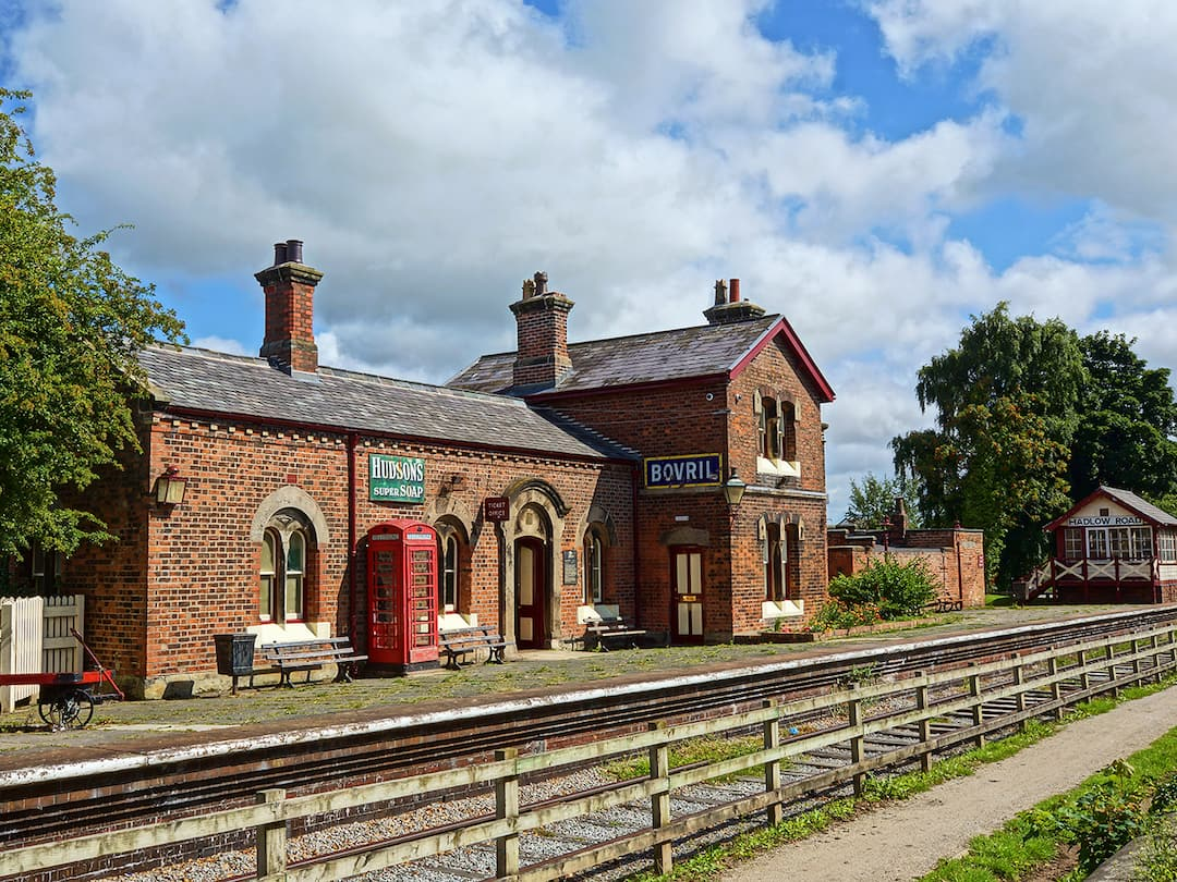 An old train station with a red telephone box on the platform
