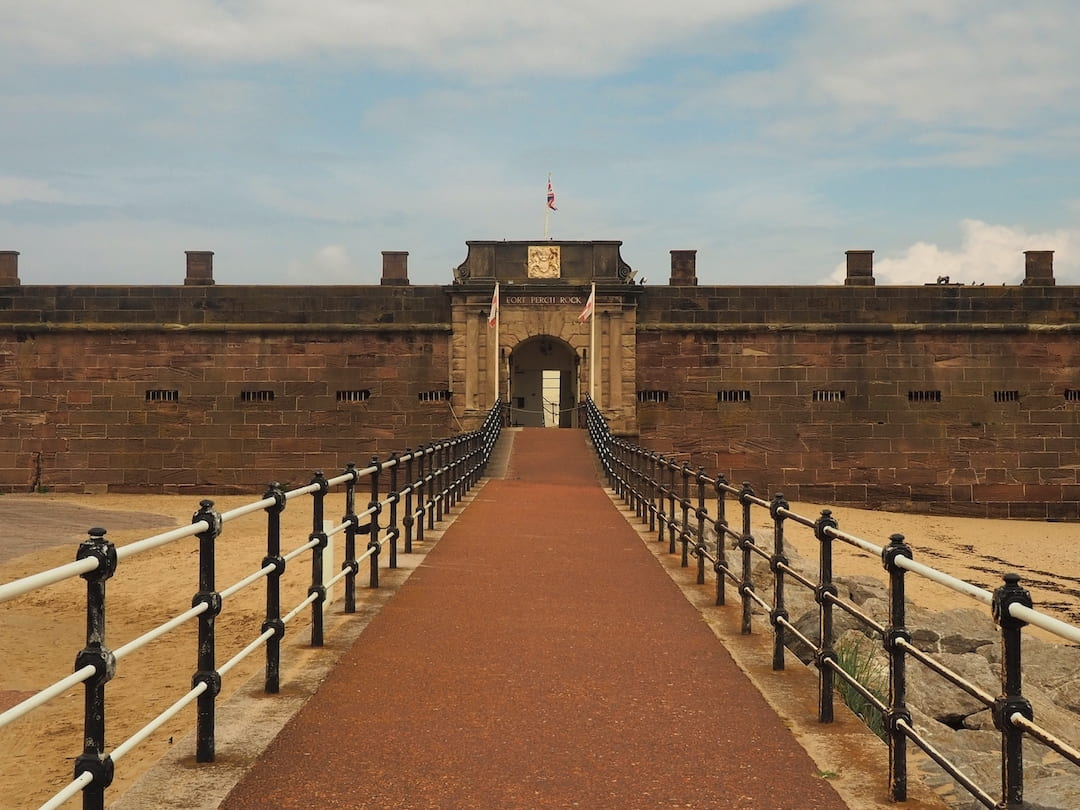 A red pathway border by railings leads to a gate at the head of a sandstone fort