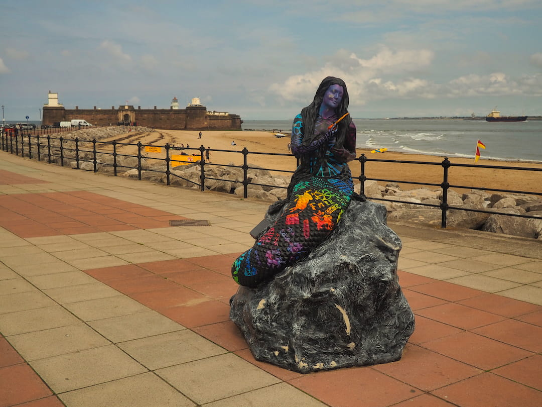 Sculpture of a mermaid on a promenade with Fort Perch Rock in the background