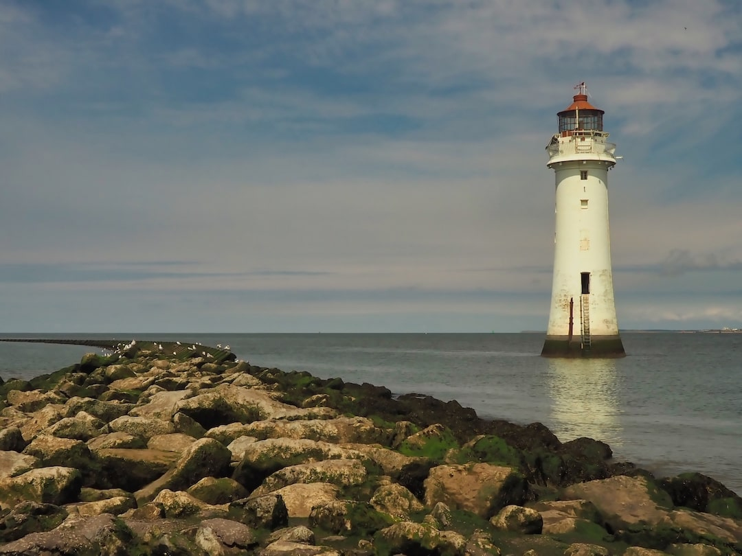 A pavement of rocks runs into the background with a white lighthouse to the right