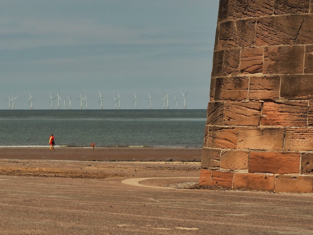 A red sandstone structure to the right, a beach, the sea and wind turbines to the left