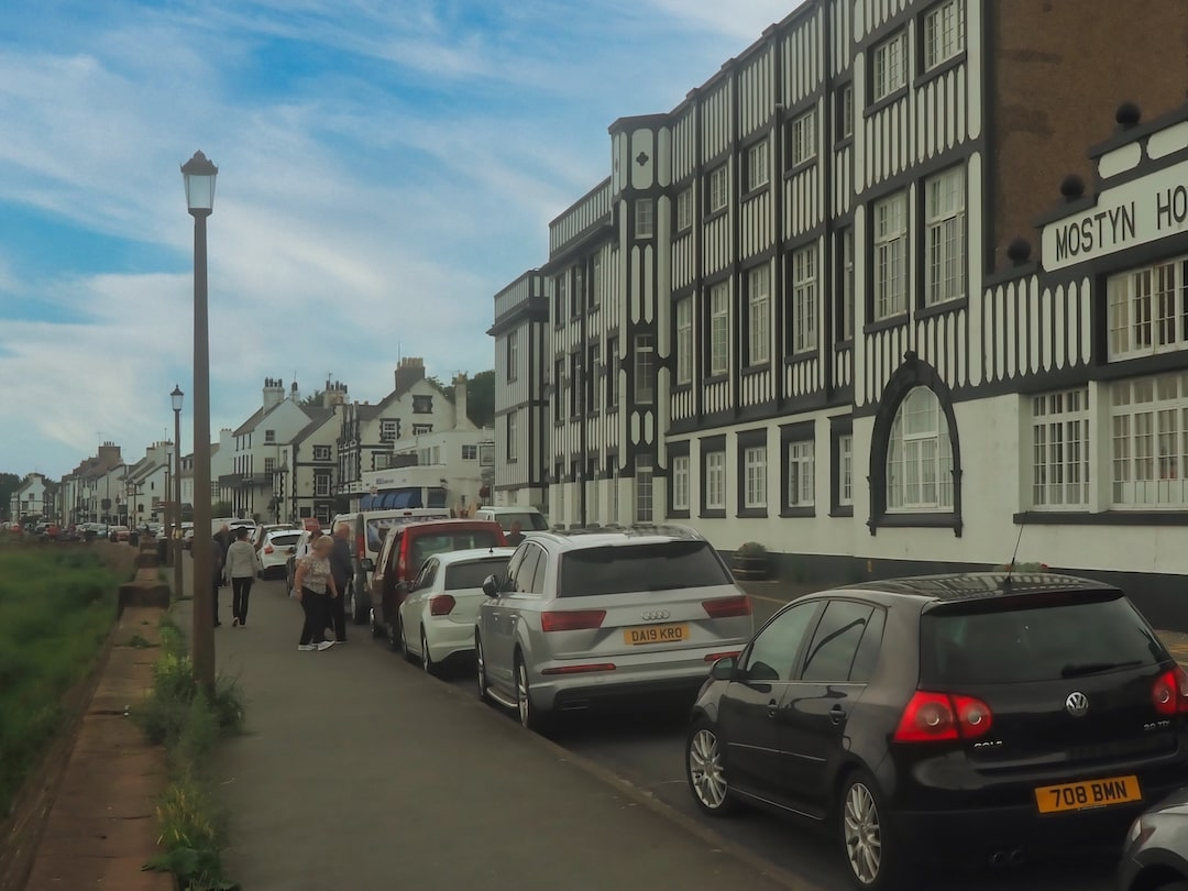 A row of cars parked on the left and a black and white building on the right