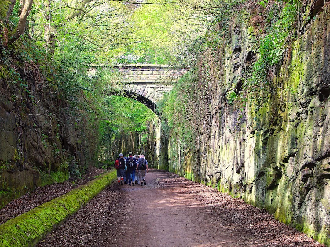 A footpath runs between two stone walls, with a stone bridge running across it in the background
