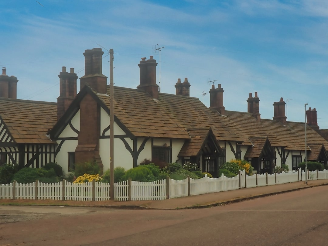 A row of cottages surrounded by low white fencing