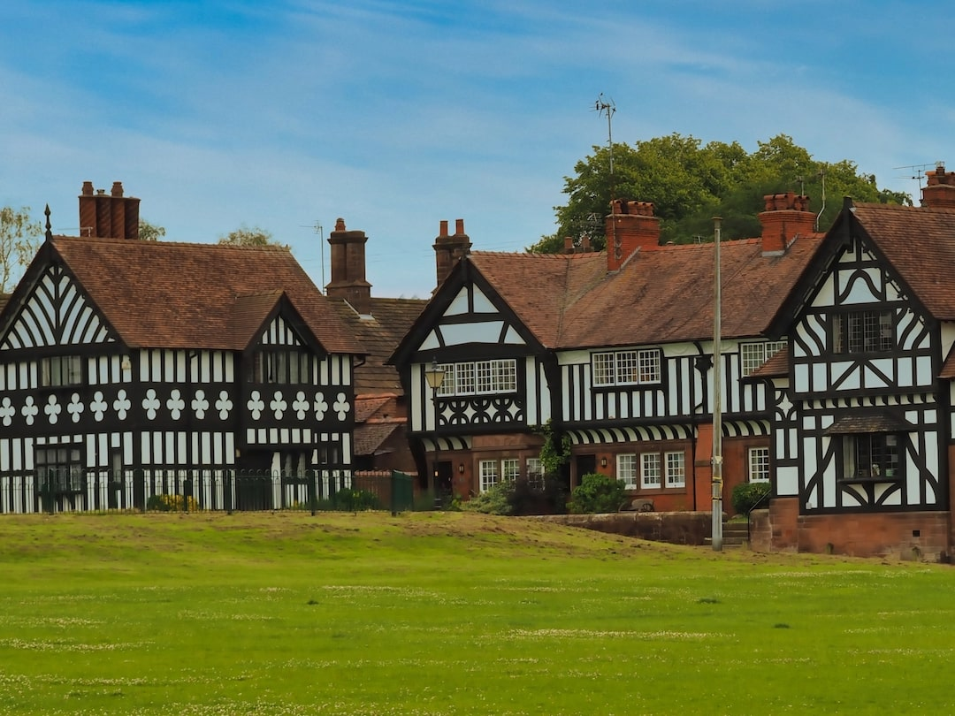 A grassy area in the foreground with black-and-white half-timbered buildings in the background