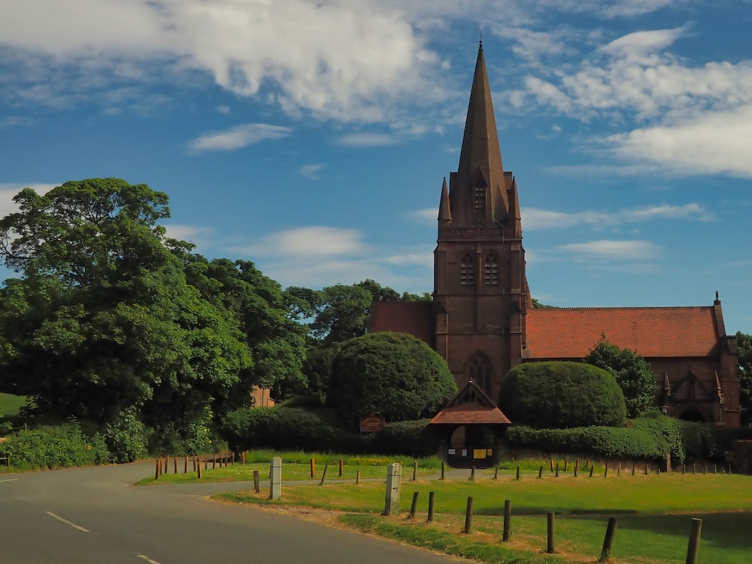 A red sandstone church with a spire, surrounded by trees