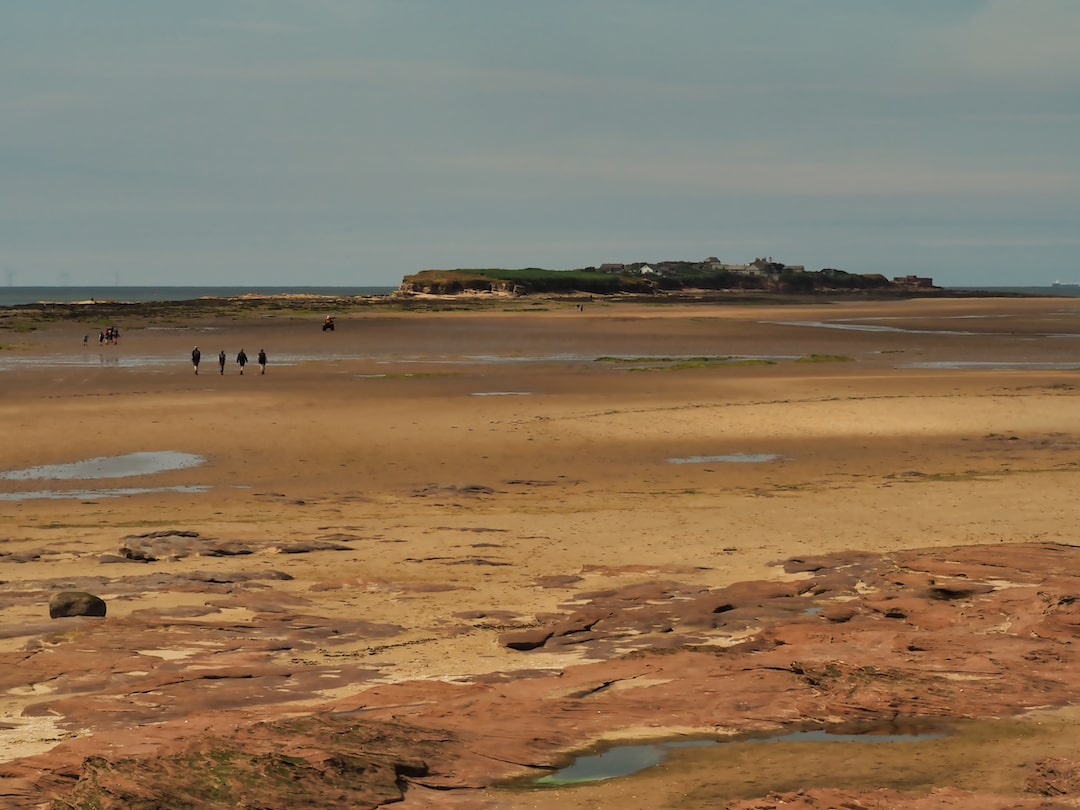 Sandstone rocks in the foregrounds beach in the middle ground and an island in the background